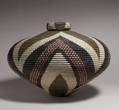 Africa |  by Beauty Nxgongo (Zulu, South Africa). ca. 1990s   || This lidded basket is an outstanding example of an important form of expression from South Africa's rural Kwazulu-Natal region. Grasses and grasslike plants are readily available natural resources in the Kwazulu-Natal region. The origins of the weaving tradition remain unknown, but European accounts describe the use of grass and related plants by the Zulu as early as the sixteenth and seventeenth centuries.