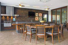 Ambientada com mesa de madeira de demolição (Depósito Kasa) e cadeiras com telinha (Decorativa). Na área da churrasqueira, a personalidade contemporânea foi acentuada pela bancada em Caesarstone (Stone Center), tijolos de demolição e coifa em inox (Refrigeração Araçatuba). O piso em porcelanato ShellStone é da Ornamentare