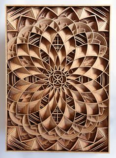 "Working with precisely cut 1/8"" pieces of laser-cut mahogany plywood, Oakland-based artist Gabriel Schama creates densely layered wood relief sculptures that twist, intersect, and overlap to create various mandala-like forms. Each piece begins as a vector illustration which is fed into his"