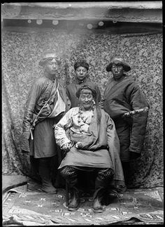 Tibet, Lhasa 1920 -21 Wealthy trader from Eastern Tibet (seated) with three servants standing behind him. The trader wears a double necklace of corals and onyx around his neck. Image is taken against a floral textile background suspended from the beams of a building. Carpet on floor.