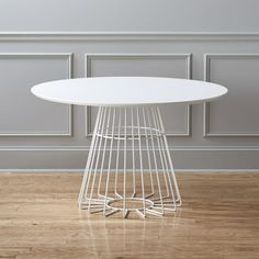 Shop compass dining table.   Sculptural diner by designer Ceci Thompson floats a modern social circle for six.  Slicked hi-gloss white, smooth round of engineered wood with beveled edge halos an airy steel pedestal base that radiates a fresh attitude.