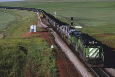 "The ""old"" Powder River - June, 1991, a Burlington Northern SD40-2 and a C30-7, lead two KCS SDs and a loaded coal train through West Antelope, Wyoming, in the Powder River Basin. An empty coal train with a caboose on the rear waits in the siding. This is triple track through here today."
