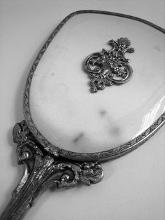 My mother had a mirror that looked exactly like this...  the handle and frame were silver as was the piece in the middle of the back of the cover.  The back itself was some kind of a pink silk textured fabric, covered by clear plastic.  The also had a brush that matched the mirror.