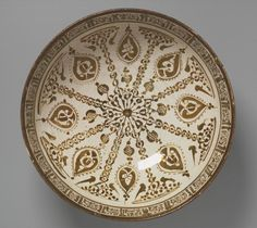 Bowl with Radial Foliate Design vessel  12th-13th century Middle East, Iran, Kashan  Seljuk-Atabeg period Persian Fritware painted with luster (copper and silver) over white lead alkali glaze opacified with tin Lusterware 9 x 21.7 cm (3 9/16 x 8 9/16 in.) [Hadji Baba Rabbi House of Antiquities, Teheran,1972], sold; to Stanford and Norma Jean Calderwood, Belmont, Massachusetts, (1972-2002), gift; to the Harvard Art Museums, 2002.