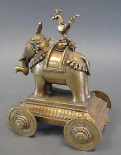Lot 88 - A BRASS ELEPHANT ON WHEELS India, 19th century forming an inkpot, the hinged stopper in the form