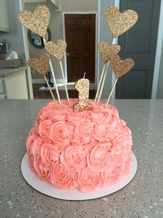 First birthday cake. Pink and gold decorations on a 1 year olds birthday cake.