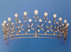 A diamond and pearl tiara, circa 1910, with eleven gold pinnacles, each topped with a pear-shaped pearl, and supported by a pair of diamond leaves, with more leaves and button pearls lower down