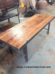 Reclaimed oak top coffee table on custom steel base leg set. Steel edging around perimeter of table. Made by Carbon Industrial Design.