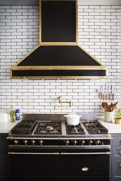 black & gold range hood on ceiling height subway tiled wall accented with black grout over black & gold range, gold pot filler