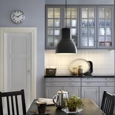 black countertop with grey ikea bodbyn cabinets and white backsplash