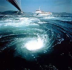 The Naruto whirlpools occur along the Shikoku coast of the Naruto Strait and are created by the large volumes of water moving between the Seto Inland Sea and the Pacific Ocean between high and low tide, combined with the unique underwater geography of the narrow strait.  © JNTO