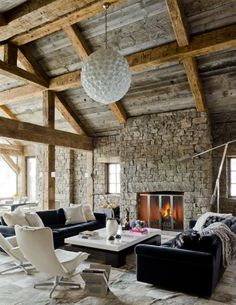 Un living con muebles y objetos contemporáneos, en negro y blanco, colores que le brindan aún más actualidad. Como marco, un espacio resuelto con madera y piedra. Estos materiales naturales y eternos, le dan al ambiente una sensación de calidez, enfatizada por la gran chimenea.