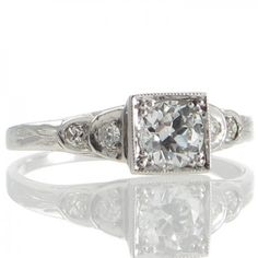 An Art Deco 18ct white gold ring featuring a 0.54ct transition cut diamond grain set within a millegrain edged square mount raised above the tapering shoulders each made as a pair of graduated curved steps each set with a single cut diamonds all tapering to a partially engraved band. #RutherfordJewellery #Melbourne