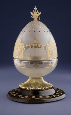 The crystal Egg standing 30cms tall is mouth-blown and hand-engraved with images of the Royal Russian family at the principal palaces in Tsarskoye Selo. To the front, Tsar Nicholas II is pictured with the Tsarina Alexandra in front of the Alexander Palace. The five children of the last Tsar and Tsarina are shown playing snowball in front of the Little Hermitage in the gardens of Catherine's Palace....