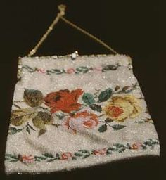 Evening bag, c. 1940s. Cream silk knitted with beads in a rose design, gilt metal mount and clasp, lined with pink silk and lace, two pockets inside.