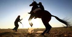 Homem saudita treina seu filho a montar cavalo em um deserto próximo a Tabuk, na Arábia Saudita