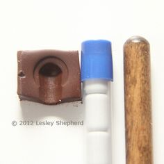 Polymer clay mold used to shape brass tape into bin pull handles in