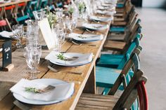 Rustic tables with hessian runners and multicoloured wooden chairs at a London warehouse wedding. Liz Linkleter Event Planning & Design. Photo Robbins Photographic