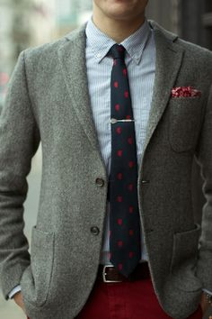 Grey herringbone jacket, white shirt with blue dress stripes, navy tie with red medallions, red pants
