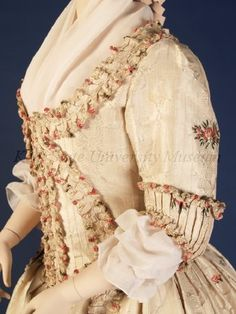 Detail side view, robe à l'Anglaise, England, 1770-1790. Ivory silk brocade woven with vertical stripes and scrolling vine, additional brocade with pinks and red flowers with green leaves scattered overall. Open robe cut away from center front to reveal underbodice, both trimmed with self-fabric robings. Worn as formal day or evening wear. Bodice and sleeves lined with natural linen.