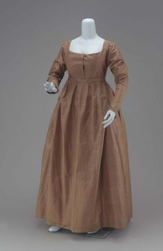 Short waisted, with front of bodice in two overlapping parts, square neck, long straight sleeves, skirt with fullness in knife pleats, less fulllness in front than in back, front panel of skirt slit from waist down about ten inches on each side of panel, but still attached to narrow waistband, ties at end of narrow waistband, of front panel to go around and tie in back thus holding up front of skirt; bodice lined with brown glazed cotton.