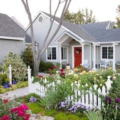 cottage style planting with picket fence and red door by dataylor