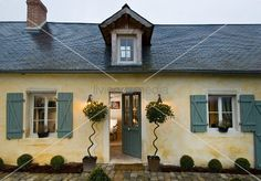 Einfaches, nordfranzösisches Landhaus mit Schieferdach, spitzer Dachgaube und eleganter Pflanzendekoration neben der Eingangstür