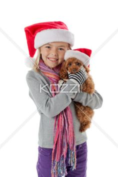 cute girl holding a brown puppy with a santa hat on. - Portrait of a cute girl holding a brown puppy over white background, Model: Alyssa Power
