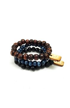 This pack of bracelets features 3 wood beaded bracelets. One black. One dark brown. One navy. Products are handmade in the USA.