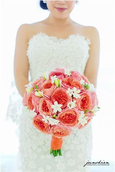 A stunning bridal bouquet of coral peonies and white stephanotis. Image credit: Junshien International Photographers.