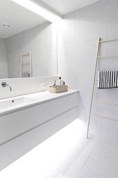 Przestrzeń tej minimalistycznej łazienki kształtuje światło. Oprawy umieszczono dyskretnie w zagłębieniu podwieszanego sufitu i pod szafką, dzięki czemu mebel zdaje się unosić w powietrzu. Ozdobą wnętrza i praktycznym dodatkiem jest bambusowa drabina-wieszak.