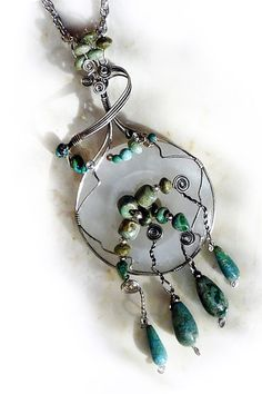 This one-of-a-kind wire wrapped pendant features many beautiful natural turquoise beads, nuggets and teardrops set in an antiqued sterling wire wrap. #handmade #OOAK #artisanjewelry