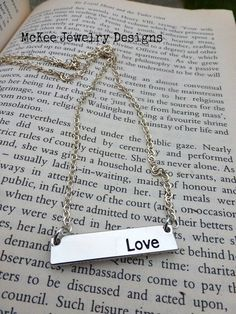 """Silver metal bar with with word """"Love"""" engraved in it and sterling silver chain necklace. McKee Jewelry Designs"""