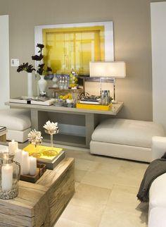 Sala com móveis moderno, mesa de centro rústica e a intensa cor do amarelo trás essa sala para o estilo contemporâneo.