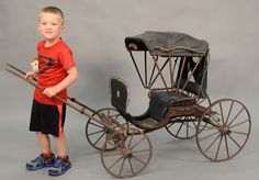 """Victorian child's pull carriage with folding top, on four wheels, marked in plate """"Christmas 1863"""".  ht. 36 in.  Estimate: $300 - $500"""