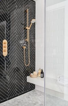 Ali Budd Interiors - Chic black and white modern bathroom boasts a seamless glass walk-in shower fitted with a marble floating bench fixed against large white beveled subway tiles above marble hex floor tiles.