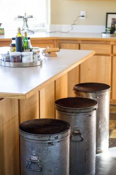 These milk cans used as bar stools in the kitchen with cowhide trimmed to fit the round tops were also found in the creamery's storage shed.   A guest house in SouthernOregon - desire to inspire - desiretoinspire.net