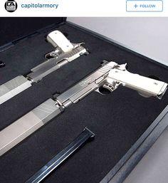 Two 1911's with white grips and white osprey supressors.