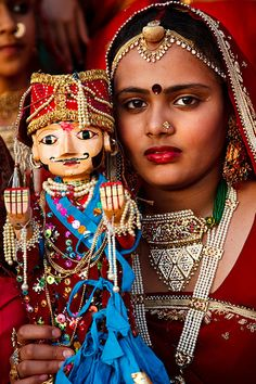 Portrait of a young girl in traditional dress holding an image of the Goddess Gauri, also known as Parvathi, during the Mewar Spring Festival, at Gangaur Ghat next to Lake Pichola.