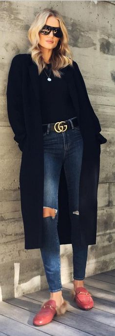 Who made  Rosie Huntington-Whiteley's black coat, flat sunglasses, gold jewelry, belt, skinny blue ripped jeans, mule shoes, and top?