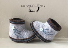 Hand-knitted blue baby booties with shooting star Chaussons de bébé tricotés à la main, bleu et marron, avec étoile filante brodée