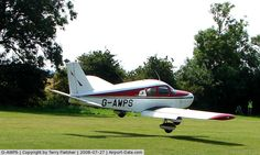 Old style red stripes on PA28-140 landing on grass strip.