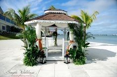 The gazebo decorated with green, tropical plants and white fabric that is tied back with burnt orange sashes at Isla Del Sol near St. Pete Beach, FL