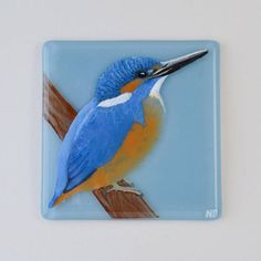 This beautiful framed, painted, fused glass Kingfisher wallhanging has been made using high quality Bullseye fusing glass, it has been hand painted with a specialist glass fusing paint, ready to be fired in the kiln for 8 hours. Once fired, the tile is adhered to a clear piece of glass at the back of the wooden box frame and a background and mount colour is picked specially to complement the piece. The frame also has a hanger on the back allowing you to hang it wherever youd wish to display…