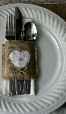 When Kelly got married we wrapped all the fork and knife in the napkin and piled it all into a basket.  I think it's be cute o wrap a strip of burlap around the napkin and tie it with twine.  Just a thought........