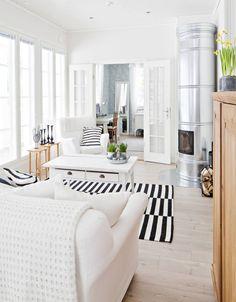 Alakerrassa ruokailutila ja olohuone ovat yhtä tilaa. Sohva ja nojatuoli ovat Ikean jo lopetettua Tomelilla-sarjaa. Myös villamatto on Ikean. Olohuoneen pöytä on peräisin Pohjanmaalta ja pieni sarjapöytä on Jaskan vanhemmilta. Pönttöuunilla lämmitetään taloa. Halkoteline Bauhausista. Pariovista näkyy työhuone, sen seinää vasten nojaavan peilin Tiina voitti työ-paikkansa arpajaisista. Työhuoneen tapetti Laura Ashley.