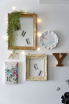 Fairylights, frames, plates and letters on wall.