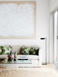 Living space with oversized artwork and glass coffee table