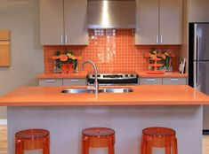 Have Ochre Ceramic Backsplash Ochre Stained Wooden Countertop White Stained Wooden Kitchen Island Transparent Ochre Acrylic Barstool Stainless Kitchen Zink Cream Stained Plastering Wall. Orange Kitchen Walls, Orange Kitchen Decor, Kitchen Colors, Wooden Kitchen, Farmhouse Kitchen Decor, Kitchen Tiles, New Kitchen, Contemporary Small Kitchens, Modern Kitchen Design