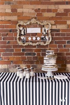 """This naked cake display with gold accents and a gold """"Mr. & Mrs."""" cake topper is stunning. Gold accents in the vintage style frame, painted gold handles of the porcelain cake serving set, and gold bow ties and sippers with the milk and cookies all dress aid in dressing up this dessert table"""